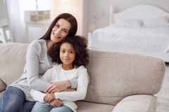 Inspired mother and daughter siting on the couch. Happy together. Attractive alert young dark-haired women smiling and hugging her daughter while sitting on the Royalty Free Stock Image