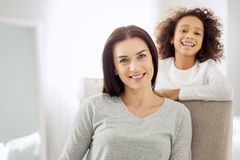 Inspired mother and her daughter behind her. Glad woman. Beautiful alert dark-haired women sitting in the arm-chair and smiling and her daughter standing behind Royalty Free Stock Photos