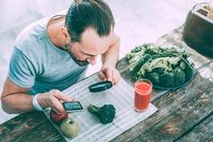 Inspired a motivé l'homme apprenant différents légumes verts images stock