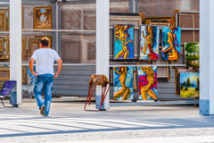 Inspired by the Muses. An unrecognizable man passes by the erotic paintings of female musicians and dancers in Vernissage of Museon park of arts of Moscow Royalty Free Stock Images