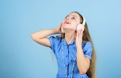 Inspired by music. Little kid listening music. Cute kid with headphones blue background. Small girl wearing stereo. Headphones. Child using technology for stock photography