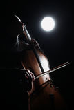 Inspired musician fine art photo. Cello player. Cellist with classical musical instrument in darkness Stock Photography
