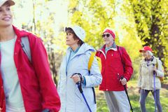 Inspired old woman hiking with her family. We are inspired. Delighted aged women hiking with her family and looking around Royalty Free Stock Images