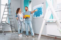 Inspired painters smiling at each other. Working process. Delighted skilled painters smiling at each other and talking about their work Royalty Free Stock Images
