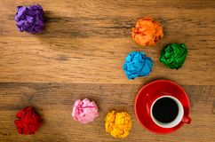 Inspired paper ball with design creation. Inspired multi colored paper ball with design creation on the copyspace area placed on the wooden desk table with a mug Royalty Free Stock Photo