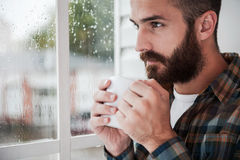 Inspired by rain. Thoughtful young bearded man holding cup with hot drink and looking through window Royalty Free Stock Photo