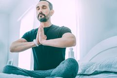 Inspired relaxed man meditating in a light room stock photography