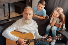 Inspired senior man playing guitar for his grandchildren. Grateful audience. Inspired elderly men playing guitar and singing for his grandchildren while they Royalty Free Stock Photos