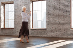 Inspired senior woman tangoing at the dance lesson. Enjoying my active hobby. Creative positive skilled senior woman performing in the ballroom while expressing Royalty Free Stock Photo