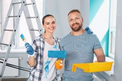 Inspired skilled painters standing together. Our best team. Exuberant professional painters smiling and holding a roller and brush Royalty Free Stock Photography