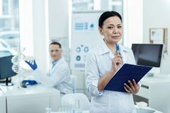Inspired smart scientist working in the lab with her colleague. Best team. Nice inspired dark-haired researcher smiling and wearing a uniform while taking notes Stock Photos