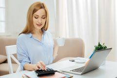 Inspired smiling businesswoman working from home. Coffee time. Beautiful self-assured successful young blond woman smiling and wearing a blue shirt while working Royalty Free Stock Image