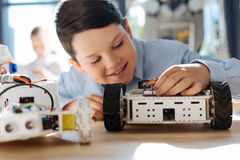 Inspired student adjusting a part in robotic vehicle. Inspiration vibes. Charming little boy sitting at the table full of robots and adjusting a small part in Royalty Free Stock Image