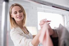 Inspired talented businesswoman choosing garments for showroom. Tailoring business. Low angle of musing appealing businesswoman putting garment on stand while Stock Photography