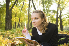 Inspired teenager girl in autumn park Stock Photos