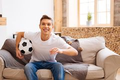 Inspired teenager holding a soccer ball. I love football. Good-looking cheerful well-built adolescent smiling and holding a soccer ball while sitting on the Royalty Free Stock Photos