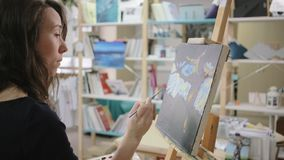 She is inspired to create a landscape painting. Young woman artist found her inspiration in nature and working on landscape painting in studio stock footage