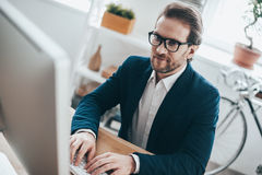 Inspired to work hard. Handsome young man in eyeglasses typing something while sitting on working place in creative office Stock Photos