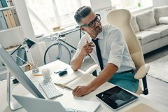 Inspired to work hard. Top view of good looking young man writing something and smiling while sitting in the office royalty free stock photos