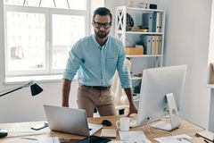 Inspired to work hard. Young modern businessman looking at camera while working in the office royalty free stock image