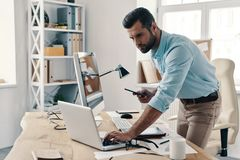Inspired to work hard. Young modern businessman using smart phone and computer while working in the office royalty free stock photos