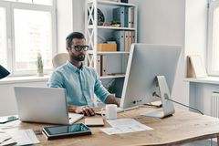 Inspired to work hard. Young modern businessman working using computer while sitting in the office stock photography
