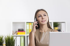 Inspired woman in beige on her phone. Portrait of an inspired businesswoman in beige sitting at her workplace in a colorful office and talking on her smartphone Royalty Free Stock Photo