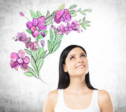 An inspired woman is dreaming about summer flowers. The sketch of purple flowers is drawn on the concrete wall stock illustration
