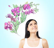 An inspired woman is dreaming about summer flowers. The sketch of purple flowers is drawn on the light blue background vector illustration