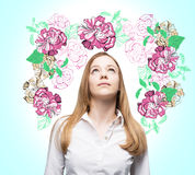 An inspired woman is dreaming about summer flowers. Stock Images