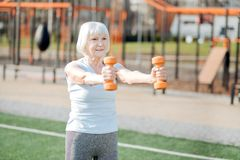 Inspired woman exercising with hand weights. I am inspired. Alert slim woman holding hand weights while exercising in the open air Royalty Free Stock Images