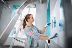Inspired woman holding a brush for painting. My idea. Pleased slim woman painting the wall in blue colour and wearing gloves Stock Images