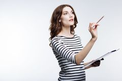 Inspired woman holding pencil and sheet holder. Upsurge of inspiration. Pleasant young woman in a striped pullover writing in the air with her pencil while Stock Images