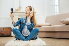 Inspired woman listening to music with her eyes closed. Favourite song. Attractive inspired blond long-haired woman smiling and sitting on the carpet with her Royalty Free Stock Photography