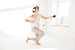 Inspired woman listening to music and imitating playing the guitar Stock Image