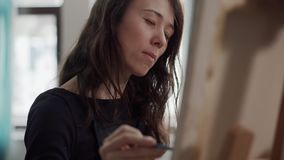 Inspired woman is painting a picture by brush, sitting in front of easel. Young brunette female artist is drawing in studio, view on her face. She is looking on stock video footage