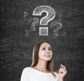 Inspired woman with a pen and question marks. Portrait of an inspired blond woman wearing white and holding a pen is standing near a blackboard with question Stock Photography