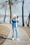 Inspired woman taking photos in the park. I like photographing. Concentrated mature woman taking pictures while walking in the park Royalty Free Stock Photos