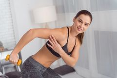 Inspired woman using hand weights while exercising. Favourite hand weights. Beautiful alert athletic dark-haired young woman smiling and holding a hand weight Royalty Free Stock Photography
