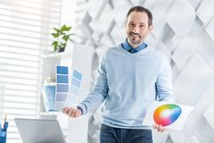 Inspired worker demonstrating some sheets of paper. Happiness. Attractive happy dark-haired bearded man smiling and holding some sheets of paper while standing Royalty Free Stock Photo
