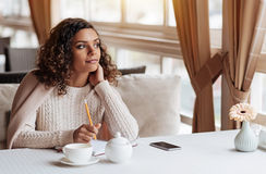 Inspired writer making notes in the cafe. Full of inspiration. Charming pleasant inspired African American woman sitting in the cafe and being covered with a Royalty Free Stock Photos