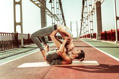 Healthy couple doing acrobatic yoga in the morning stock photography