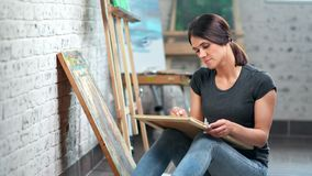 Inspired young charming female painter drawing picture on canvas at art studio. Medium long shot. Beautiful skilled woman artist sketching image using pencil stock footage
