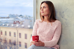 Inspired young girl holding a cup of coffee and looking through. Close-up of inspired young girl sitting on the windowsill. Holding a cup of coffee and admiring Stock Image