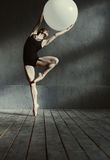 Inspired young gymnast stretching using the white ball Stock Images
