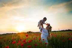 Inspired young mother. Happy motherhood, a young women in a wildflower wreath with her little daughter walking in the poppy field on a sunset. Inspired nature Royalty Free Stock Photography