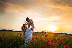 Inspired young mother. Happy motherhood, a young women in a wildflower wreath with her little daughter walking in the poppy field on a sunset. Inspired nature Stock Photography