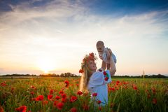 Inspired young mother. Happy motherhood, a young women in a wildflower wreath with her little daughter walking in the poppy field on a sunset. Inspired nature Stock Photos
