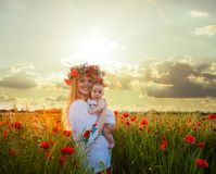 Inspired young mother. Happy motherhood, a young women in a wildflower wreath with her little daughter walking in the poppy field on a sunset. Inspired nature Royalty Free Stock Photo
