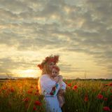 Inspired young mother. Happy motherhood, a young women in a wildflower wreath with her little daughter walking in the poppy field on a sunset. Inspired nature Royalty Free Stock Photos